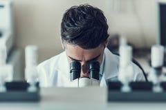 Jeune scientifique à l'aide du microscope dans le laboratoire photographie stock libre de droits