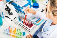 Jeune scientifique attirant de femme travaillant avec des tubes à essai dans Photo stock