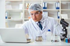 Jeune scientifique de chercheur faisant un expe de contamination d'essai d'eau images libres de droits