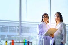 Jeune scientifique féminin se tenant avec le techer dans la fabrication de technicien de laboratoire photographie stock