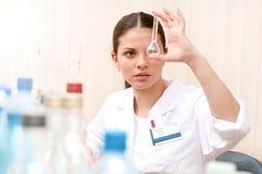 Jeune scientifique féminin tenant le tube à essai et le regardant dans le laboratoire image stock