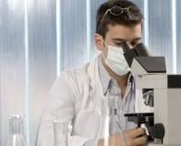 Jeune scientifique observant à l'intérieur d'un microscope Image stock