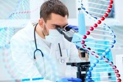 Jeune scientifique regardant au microscope dans le laboratoire images stock