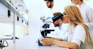 Jeune scientifique regardant par le microscope dans le laboratoire photographie stock libre de droits