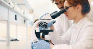 Jeune scientifique regardant par le microscope dans le laboratoire photo libre de droits