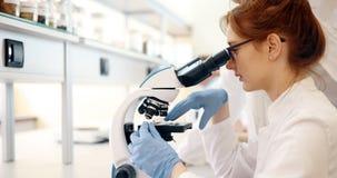 Jeune scientifique regardant par le microscope dans le laboratoire photo stock