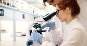 Jeune scientifique regardant par le microscope dans le laboratoire image libre de droits