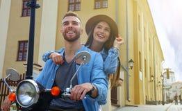 Jeune scooter heureux d'équitation de couples en ville Voyage beau de type et de jeune femme Concept d'aventure et de vacances Image libre de droits