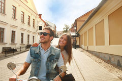 Jeune scooter heureux d'équitation de couples en ville Voyage beau de type et de jeune femme Concept d'aventure et de vacances Photo stock