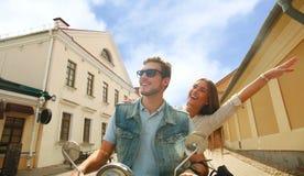 Jeune scooter heureux d'équitation de couples en ville Voyage beau de type et de jeune femme Concept d'aventure et de vacances Photos libres de droits
