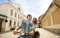 Jeune scooter heureux d'équitation de couples en ville Voyage beau de type et de jeune femme Concept d'aventure et de vacances Photographie stock