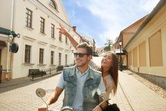 Jeune scooter heureux d'équitation de couples en ville Voyage beau de type et de jeune femme Concept d'aventure et de vacances Image stock