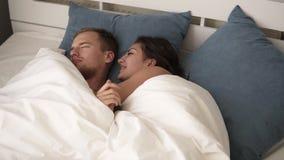 Jeune se réveiller de sourire de femme de brune heureux après le sommeil sain s'étendant sur le lit confortable avec l'homme de s banque de vidéos
