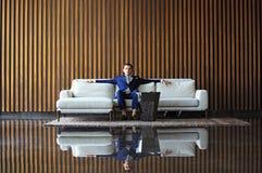 Jeune se reposer heureux d'homme d'affaires décontracté sur le sofa au lobby d'hôtel utilisant le smartphon, attendant quelqu'un Photographie stock