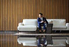 Jeune se reposer heureux d'homme d'affaires décontracté sur le sofa au lobby d'hôtel utilisant le smartphon, attendant quelqu'un Photo libre de droits