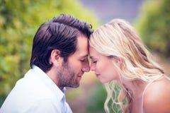 Jeune se reposer heureux de couples face à face Photos stock