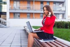 Jeune se reposer professionnel de femme d'affaires extérieur avec l'ordinateur Image libre de droits