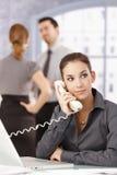 Jeune secrétaire au téléphone dans le bureau Images libres de droits