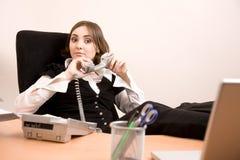 Jeune secrétaire avec le téléphone et l'ordinateur portatif Photos stock