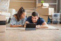 Jeune sentiment de couples amusé dans leur nouvelle maison image stock