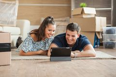 Jeune sentiment de couples amusé dans leur nouvelle maison photographie stock