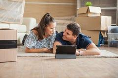Jeune sentiment de couples amusé dans leur nouvelle maison image libre de droits