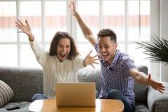 Jeune sentiment de couples excité par la victoire en ligne regardant l'ordinateur portable images libres de droits