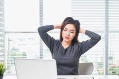 Jeune sentiment ennuyé de femme assoupi au bureau se reposant avec l'ordinateur portable image libre de droits