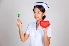 Jeune seringue asiatique de prise d'infirmière et coeur rouge Photo stock