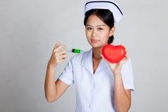 Jeune seringue asiatique de prise d'infirmière et coeur rouge Images libres de droits