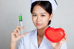 Jeune seringue asiatique de prise d'infirmière et coeur rouge Photos stock