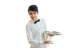 Jeune serveur attirant un penchement de sourire de chemise blanche en avant et en tenant un plateau Photo stock