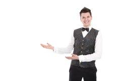 Jeune serveur ou maître d'hôtel de sourire faisant des gestes l'accueil - d'isolement sur W Photo stock