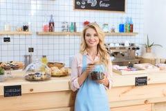 jeune serveuse attirante tenant des grains de café dans le pot en verre et souriant à l'appareil-photo photographie stock