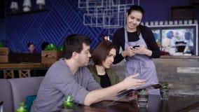 Jeune serveuse de sourire se tenant en café près de la table des couples heureux et mettant leur ordre dans le comprimé numérique banque de vidéos