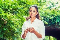Jeune service de mini-messages américain indien est de femme au téléphone portable extérieur au Central Park, New York image stock