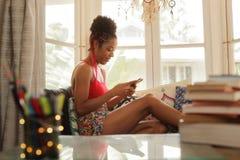 Jeune service de mini-messages de femme de couleur sur le téléphone et le sourire Images libres de droits