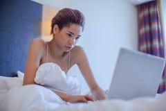 Jeune siège de femme de couleur dans le lit Photo libre de droits