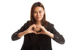 Jeune signe asiatique de main de coeur d'exposition de femme d'affaires Photos stock