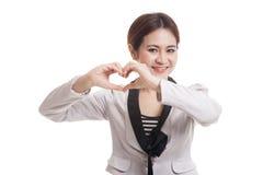 Jeune signe asiatique de main de coeur d'exposition de femme d'affaires Image stock