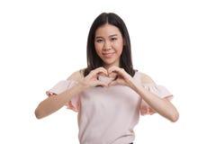 Jeune signe asiatique de main de coeur d'exposition de femme d'affaires Photographie stock