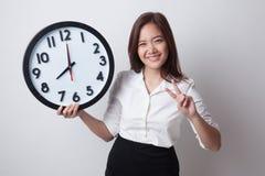 Jeune signe asiatique de victoire d'exposition de femme d'affaires avec une horloge Images libres de droits