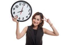 Jeune signe asiatique de victoire d'exposition de femme d'affaires avec une horloge Image stock