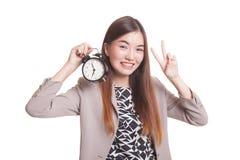 Jeune signe asiatique de victoire d'exposition de femme d'affaires avec une horloge Photos libres de droits