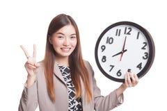 Jeune signe asiatique de victoire d'exposition de femme d'affaires avec une horloge Photo libre de droits