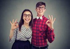 Jeune signe drôle d'ok de showig de couples exprimant l'excitation photos stock