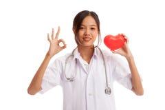 Jeune signe femelle asiatique d'OK d'exposition de docteur avec le coeur rouge Photographie stock libre de droits