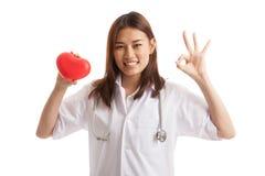 Jeune signe femelle asiatique d'OK d'exposition de docteur avec le coeur rouge Photo stock