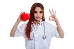 Jeune signe femelle asiatique d'OK d'exposition de docteur avec le coeur rouge Photos stock