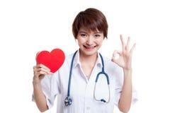 Jeune signe femelle asiatique d'OK d'exposition de docteur avec le coeur rouge Images stock